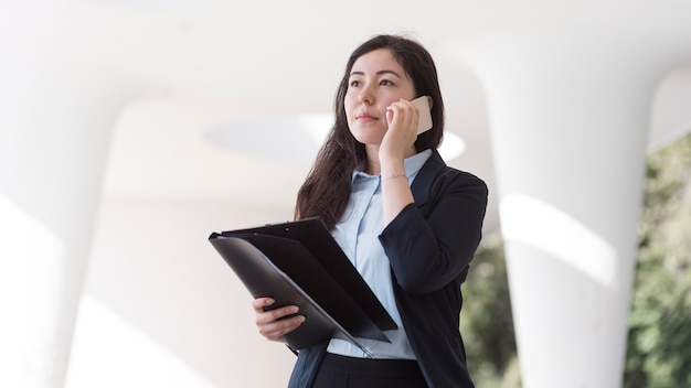 Деловая женщина разговаривает по телефону под низким углом