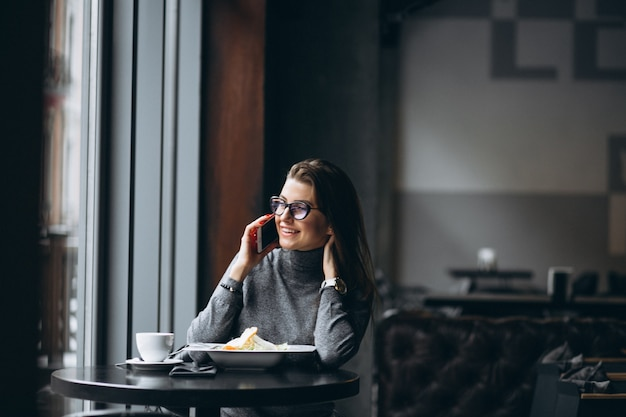 Business woman talking on a phone and eating salad in a cafe