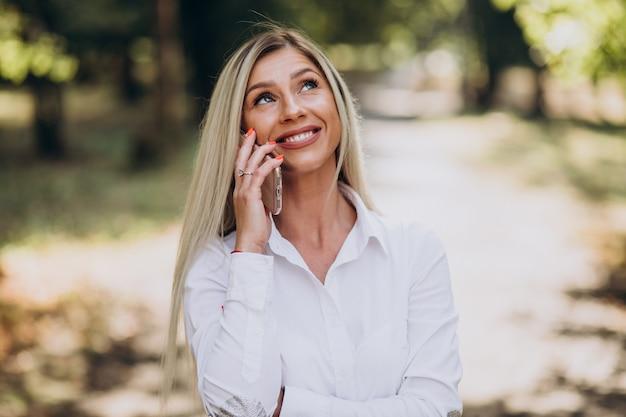 Donna di affari che parla al telefono nel parco