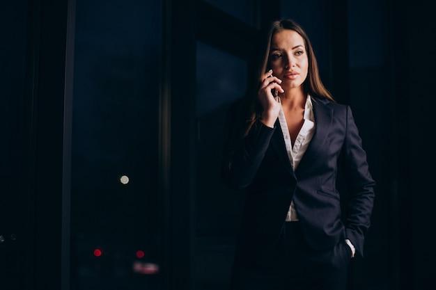 Donna d'affari che parla al telefono e resta fino a tarda notte in ufficio