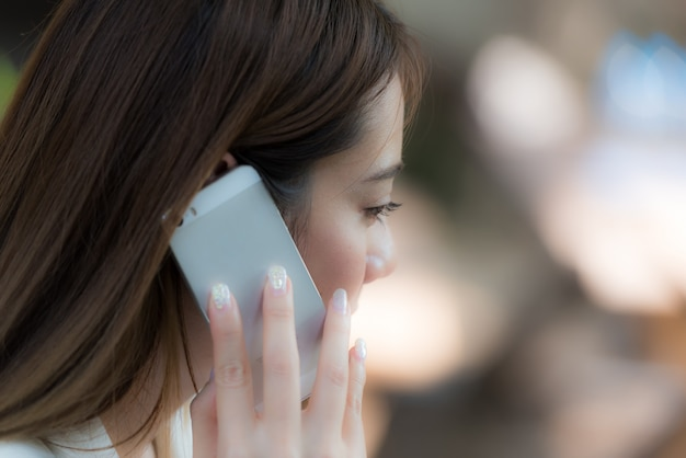 Business woman talking on smartphone on natural background, close up.