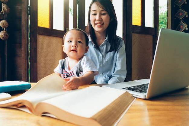Business woman teaching her child with multimedia and book, home school.