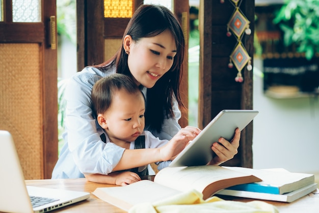 Business woman teaching her son with laptop, tablet, and book, home school education.
