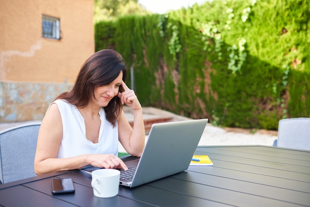 집 정원에서 야외에서 노트북을 들고 재택근무하는 비즈니스 여성