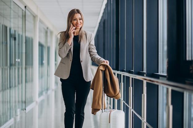 Donna di affari in terminale con la borsa di viaggio che parla sul telefono