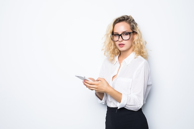 Business woman texting on her mobile phone isolated over white wall