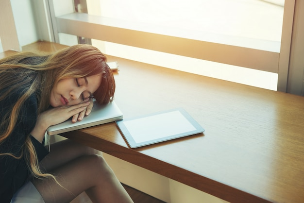 Business woman tired a sleep on the office room while working.