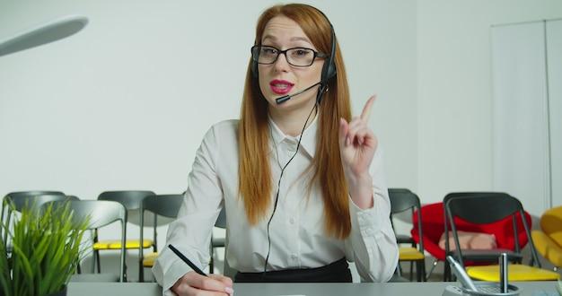 마이크가있는 헤드셋의 비즈니스 여성 트레이너 교사가 카메라 기록 온라인 마스터 클래스 웹 세미나를 찾습니다.