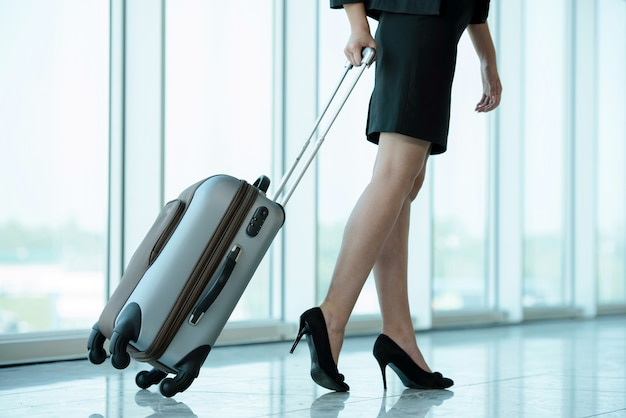 Business woman traveling with trolley.