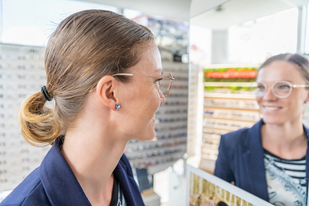 Business woman tries glasses in front of a mirror in an optics store