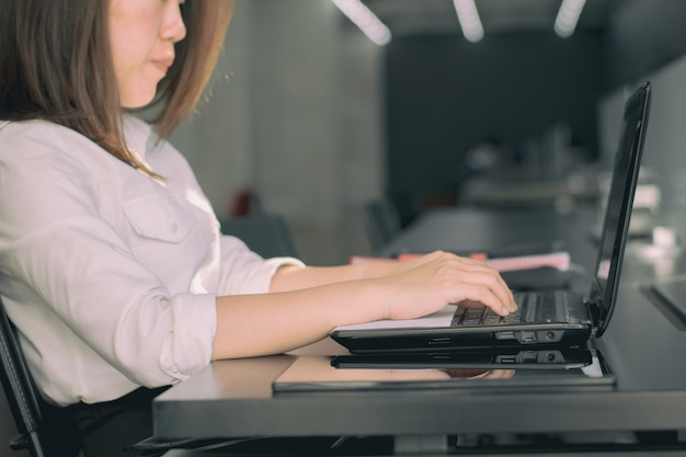 Business woman typing on laptop keyboard