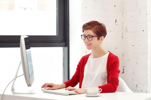 明るいオフィスでキーボードで入力するビジネスの女性。