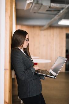 ビジネスの女性が壁にノートパソコンのキーボードで入力します。
