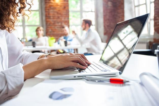 Деловая женщина печатает отчет и принимает к сведению на ноутбуке во время встречи с боссом, вид сбоку женских рук, печатающих на клавиатуре ноутбука на рабочем месте, секретарь, работающий с компьютером в домашнем офисе,