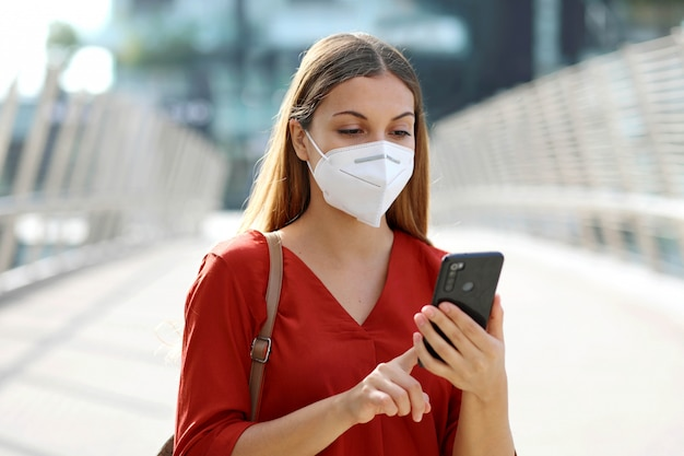 Business woman typing on smart phone in modern city wearing face mask protection