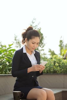 Business woman use smartphone at the garden park