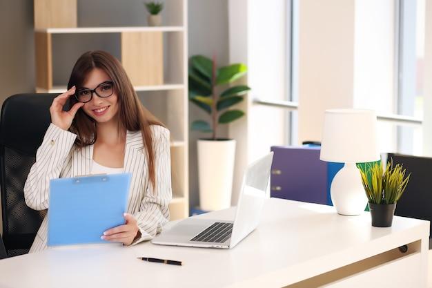 비즈니스 여자는 사무실에서 작업하는 동안 노트북과 미소를 사용합니다.