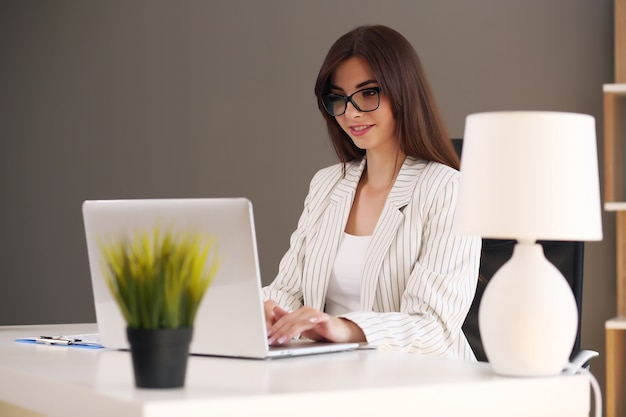 Business woman uses a laptop and smiles while working in the office.