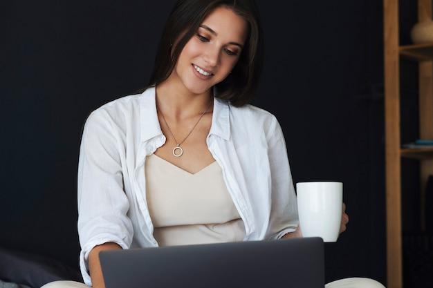 ビジネスウーマンはラップトップを使用し、自宅からリモートで作業します。白いシャツを着た笑顔の女の子が彼女の手にコーヒーのカップを持って、ベッドに座っています。