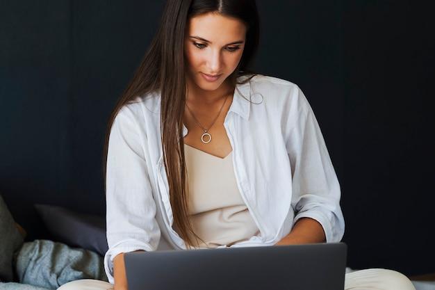 ビジネスウーマンはラップトップを使用し、自宅からリモートで作業します。白いシャツを着た笑顔の女の子は、ラップトップの隣のベッドに座っています。寝室の壁の暗い壁に美しいブルネット。