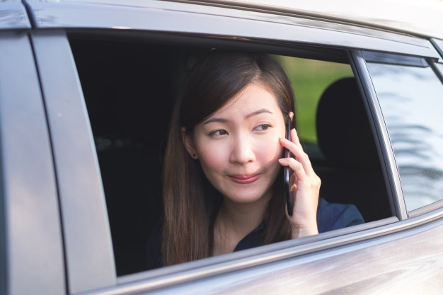 Business woman uses smartphone while riding a car