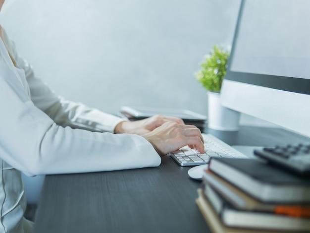 オフィスの黒いテーブルでコンピューターを使用してビジネス女性
