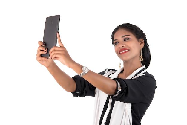 흰 벽에 고립 된 휴대 전화 또는 스마트 폰을 사용하는 비즈니스 우먼