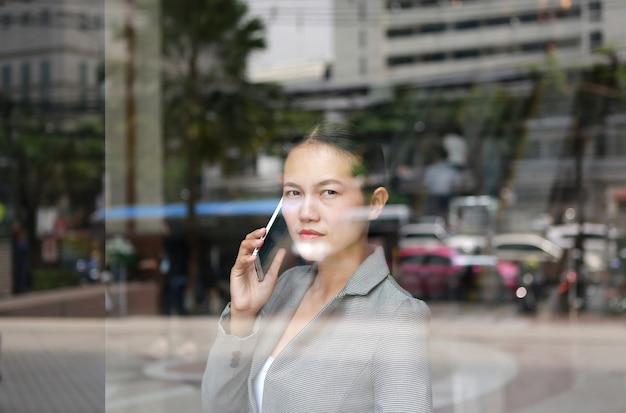 オフィスビルの反射ガラスでスマートフォンを使用しているビジネス女性。