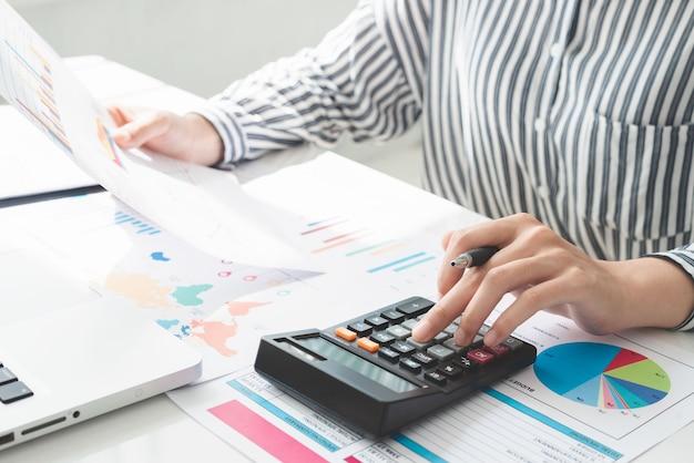 계산기를 사용하고 작성하는 비즈니스 여성은 계산과 함께 메모를 작성합니다. 세금과 경제 개념.