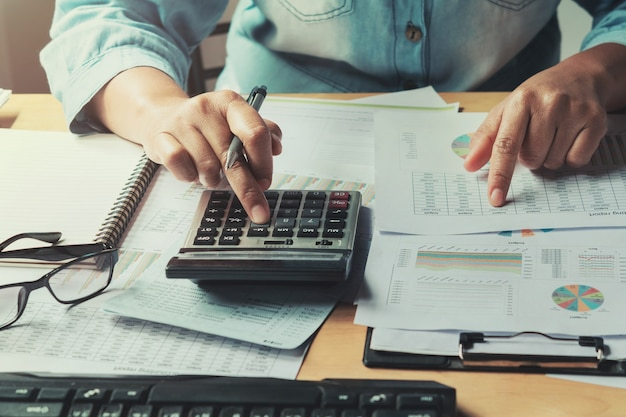Business woman using calculator to calculate of data document finance accounting in office