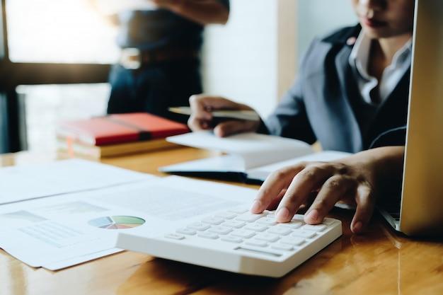 電卓を使用してビジネスの女性はオフィスとビジネスの作業背景、税金、会計、統計、分析研究の概念の木製の机の上の数学金融を行う