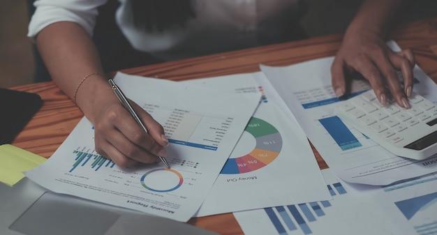 計算機を使用して、オフィスやビジネスの仕事の背景、税務、会計、統計、分析研究の概念の木製の机の上で数学ファイナンスを行う