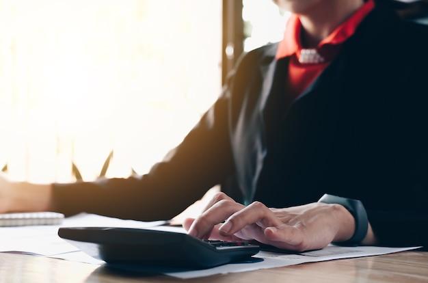 ビジネスの女性は、計算機を使用して、オフィスで木製の机の上で数学金融を行う