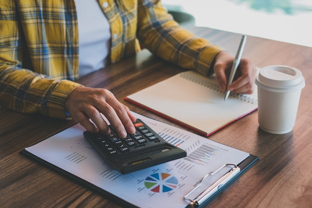 Business woman using calculator with analysis charts and graphs business report and writing on notebook in office