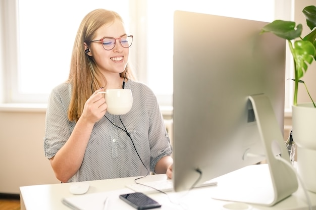 Business woman using computer at home, office, cup of caffe. high quality photo