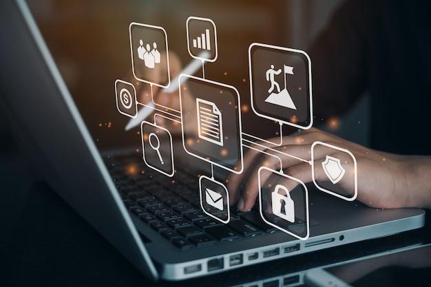 가상 아이콘이 있는 컴퓨터를 사용하는 비즈니스 우먼. 사무실의 랩톱 컴퓨터에서 작업 중인 문서 관리 시스템(dms)이 설정되고 있습니다. 디지털 마케팅.