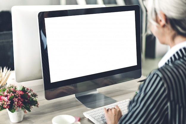 Business woman using computer with white mockup blank screens in modern work loft
