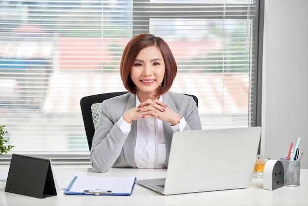 Деловая женщина, используя свой портативный компьютер в офисе. деловые люди