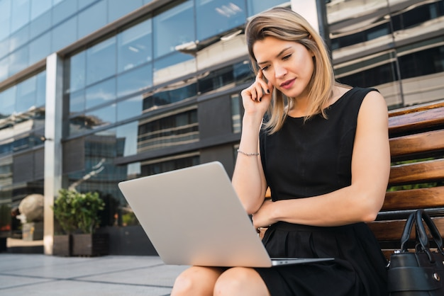 Business woman using her laptop outdoors.