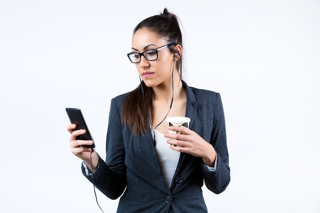 Business woman using her mobile phone and drinking coffee.