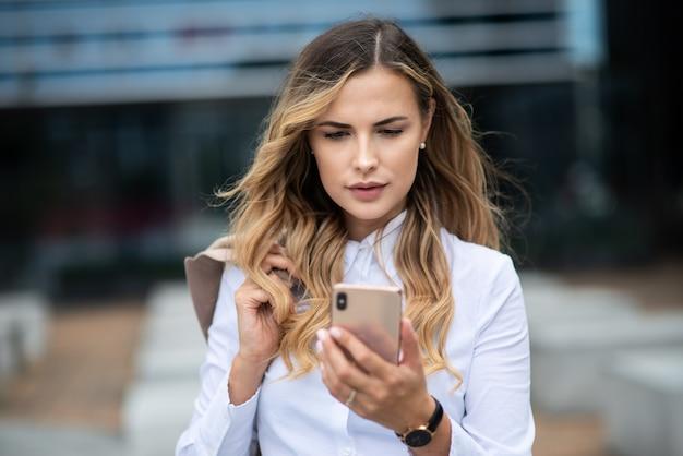 그녀의 사무실 건물 앞에서 그녀의 휴대 전화를 사용하는 비즈니스 우먼