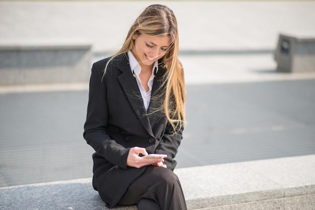 街の通りで屋外に座っている間彼女の携帯電話を使用してビジネス女性