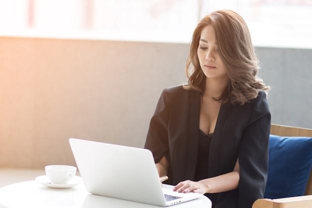 랩톱 컴퓨터를 사용하는 비즈니스 여자. 야외 카페에서 노트북에서 일하는 여성.