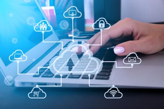 아이콘이 있는 가상 클라우드 기술로 노트북 컴퓨터를 사용하는 비즈니스 여성. 클라우드 기술 빅데이터 관리에는 비즈니스 전략, 고객 서비스가 포함됩니다. 고품질 사진
