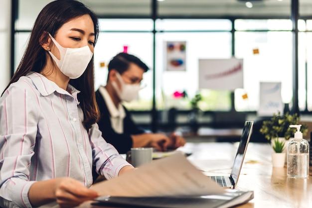 社会的な距離で保護マスクを着用して作業ラップトップコンピューターを使用してビジネス女性