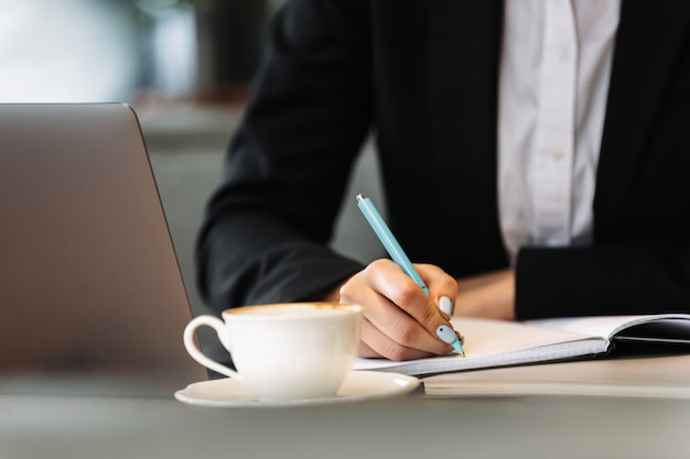 Business woman using laptop computer writing notes
