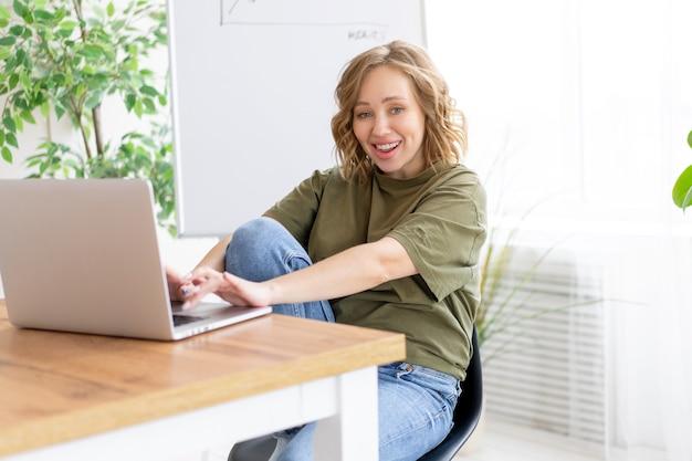 Деловая женщина, использующая ноутбук, сидя на столе, белый офисный интерьер с комнатным растением, глядя на камеру