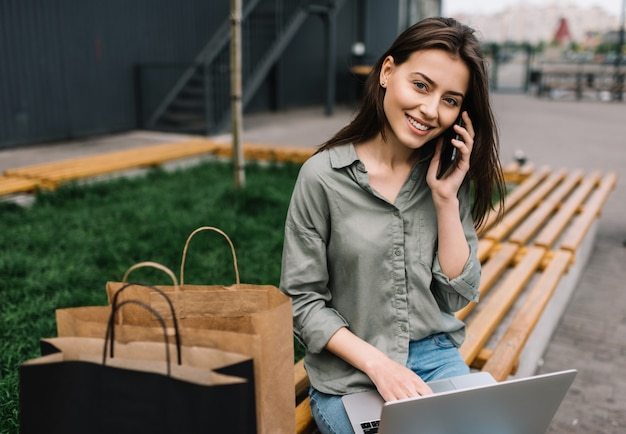 Business woman using laptop, talking on mobile phone