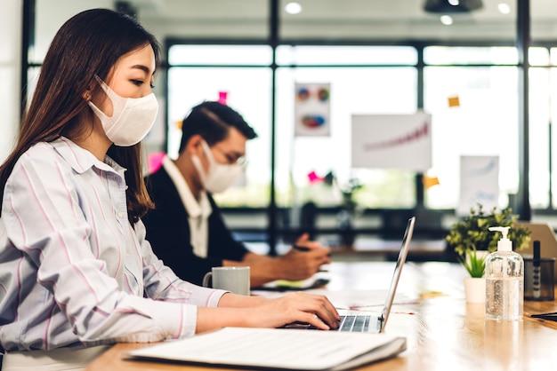 オフィスでフェイスマスクを使用してラップトップを使用してビジネス女性