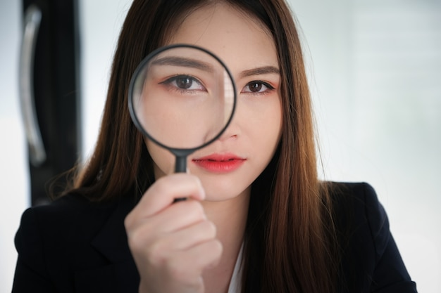 Business woman using magnifying to using audit or scan concept.